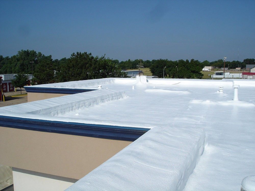A completed white commercial roofing project.